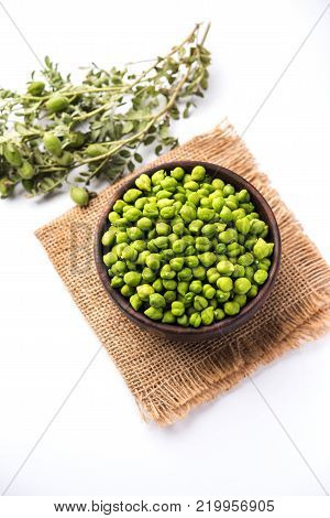 Fresh Green Chickpeas or Chick peas also known as harbara or harbhara in hindi and Cicer is scientific name, served in a wooden bowl