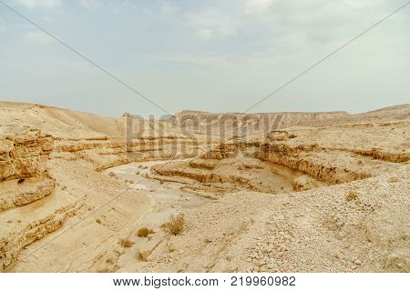 Scenic landscape view from cliff on dry desert in Israel. Valley of sand, rocks and stones in hot middle east tourism place. Scenic outdoor view on wild land. Summer heat and sunlight, nobody on photo