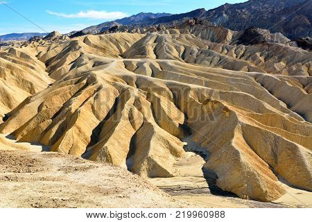 Golden badlands eroded into waves, pleats and gullies at Zabriskie Point in the Death Valley National Park in USA.