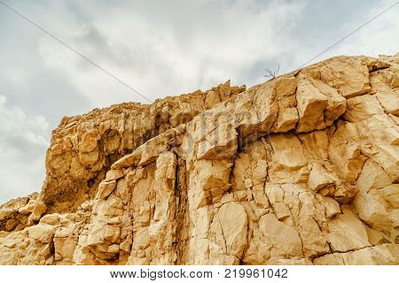 View on stone rock in dry desert in Israel. Valley of sand, rocks and stones in hot middle east tourism place. Scenic outdoor view on wild mountain. Summer heat and sunlight, nobody on photo