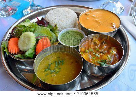 Plate of lamb tikka masala, served with aaloo mattar, lentil, rice, naan, and salad.