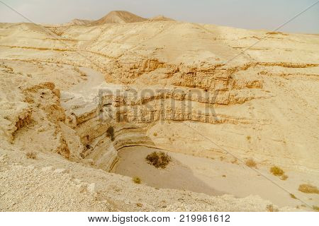 Landscape scenic view from cliff on dry desert in Israel. Valley of sand, rocks and stones in hot middle east tourism place. Scenic outdoor view on wild land. Summer heat and sunlight, nobody on photo