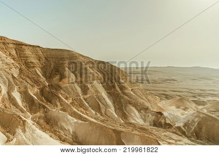 Landscape of mountain hill in dry desert in Israel. Valley of sand, rocks and stones in hot middle east tourism place. Scenic outdoor view on wild land. Summer heat and sunlight with nobody on photo