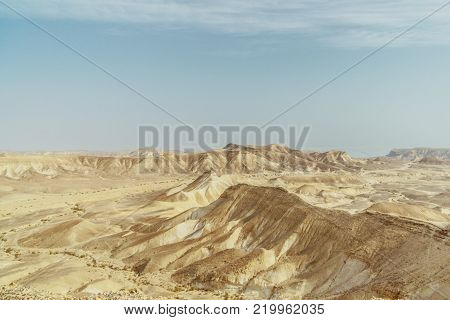 View from canyon on landscape of dry desert in Israel. Valley of sand, rock and stone in hot middle east tourism place. Scenic outdoor view on wild land. Summer heat and sunlight with nobody on photo