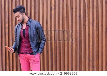Young Arab pleasant appearance reads and writes message, smiling looking to side, makes appointment and looks forward to important person, smiling guy posing and shooting for advertising men's contemporary clothing