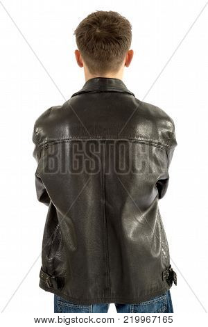 18 year old wearing a leather jacket and jeans facing away isolated on white background