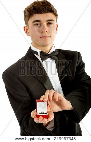 18 year old wearing a tuxedo smiling oepning a ring box isolated on a white background