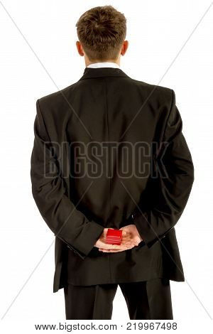 18 year old wearing a tuxedo hiding a ring box behind his back isolated on a white background