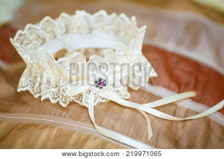 Decorated white wedding garter on sofa. Marriage concept