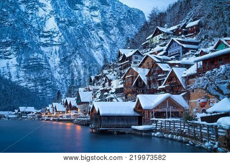 Classic postcard view of traditional wooden houses in famous Hallstatt lakeside town in the Alps in mystic twilight during blue hour at dawn on a beautiful cold foggy day in winter, Salzkammergut region, Austria
