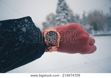 A man's hand with a gilded clock against a snowfall in the town