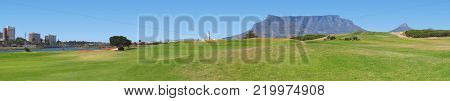 PANORAMIC LANDSCAPE, OF MOUNTAINS AND BUILDINGS  IN THE BACK GROUND, AND LAWN RIGHT ACROSS THE FORE GROUND