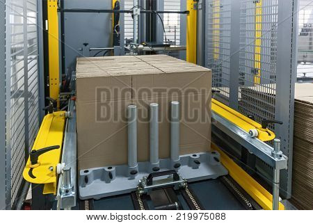 Strapping Machine for Industrail Packaging Line, Modern machine for packaging line in factory, Industrial and technology concept.