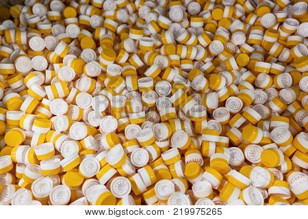 background of plastic bottle caps. plastic caps for bottles of yellow and white. The production process is a line for the packaging of plastic bottles.
