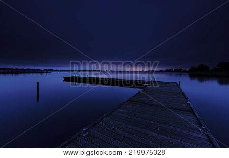 Wooden platform in a calm lake under a blue night sky with first light at the horizon