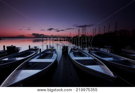 Small motorboats lying still at a platform in a calm lake under a purple and orange dawn