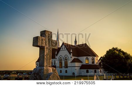 church and stone cross at sunset in prince edward island