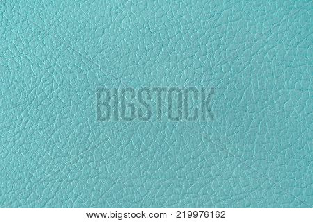Texture of artificial leather. Turquoise background or leatherette backdrop. Fine embossing.