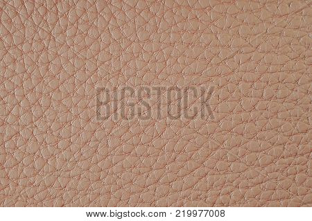 Texture of artificial leather. Orange-red background or leatherette backdrop.