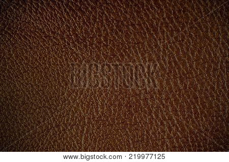 Texture of artificial leather. Dark brown background or leatherette backdrop with a glint of light or vignette.