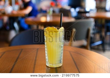 Glassy faceted glass stands on wooden table with black drinking straw, which been poured tea, lemonade, yellow drink with lemon and ginger. Concept of alcoholic and non-alcoholic drinks, waiting for someone, lunch break , cafe network.