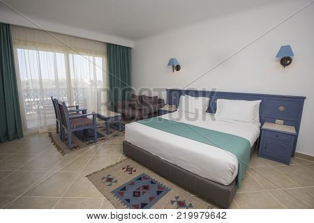 Double bed in suite of a luxury hotel room with lounge and curtains