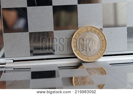 Turkish coin in mirror reflect wallet lies on wooden bamboo table background Denomination is one lira - back side