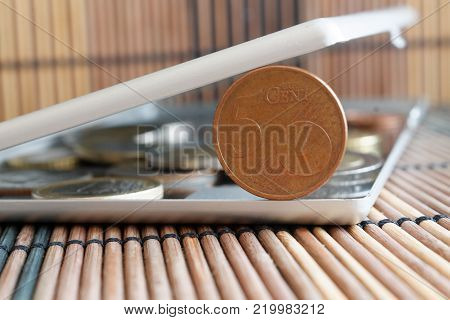 Pile of Euro coins in mirror reflect wallet lies on wooden bamboo table background Denomination is five euro cents