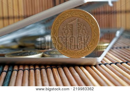Turkish coins in mirror reflect wallet lies on wooden bamboo table background Denomination is one lira