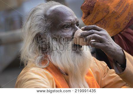 BABUGHAT, KOLKATA, WEST BENGAL / INDIA - 10TH JANUARY 2015 : Portrait of Hindu Sadhu with white beard, drinking tea.