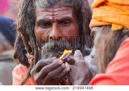 BABUGHAT, KOLKATA, WEST BENGAL / INDIA - 10TH JANUARY 2015 : Hindu Sadhu lighting up marijuana for another Sadhu, locally called Ganja, a form of canabis sativa .