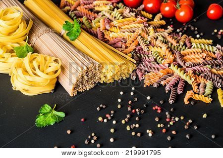 Various kind of italian raw Pasta. colorful fusilli pasta, spaghetti, fettuccine with tomatos on a black background. Closeup.