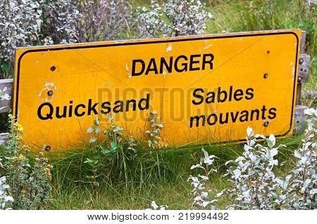 Closeup of a bilingual danger quicksand sign.