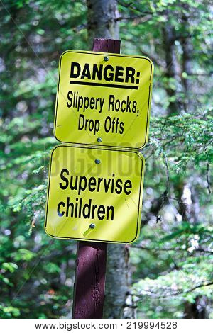 Danger slippery rocks, drop offs and supervise children sign.