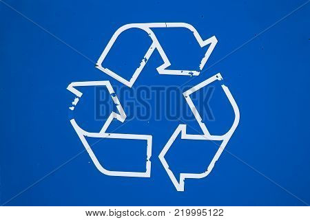 Closeup of a worn recycle sign on a blue background.
