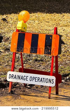 A small drainage operations obstruction sign in spring.