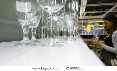 Blurred Caucasian girl chooses glasses at the hardware store, 4K.