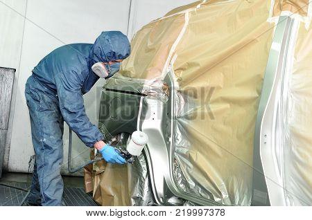 Professional car painter spraying a silber car.