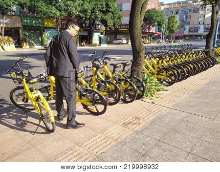 ZHONGSHAN;GUANGDONG;China-December 1;2017:office gentleman ready to ride a shared bike.Bicycle-sharing is very popular in China.
