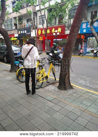 ZHONGSHAN,GUANGDONG,China-November 24,2017:girl prepaing to ride a shared bike.Bicycle-sharing is very popular in China.