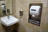 Hand wash sink and dryer blower in public restroom poster
