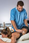 Chiropractic treatment. Woman patient. Male chiropractor. Color image poster