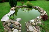 Beautiful classical design garden fish pond in a well cared backyard gardening background poster
