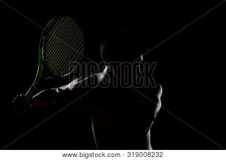 Young  shirtless Tennis player ready to swing  a racquet isolated on a dark background