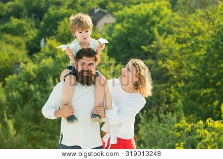 Family Holiday And Togetherness. Happy Joyful Family Having Fun Throws Up In The Air Little Boy Chil