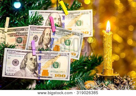 Candle In Front Of The Christmas Tree, Which Is Decorated With Dollars. Wishes For Wealth In The New