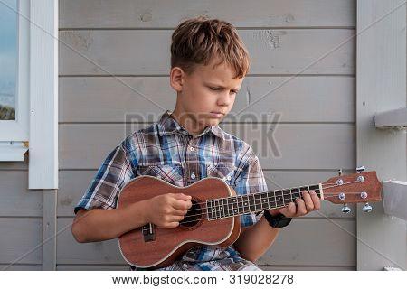 Cute Boy Of European Appearance Plays Ukulele On Summer Terrace