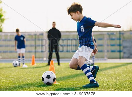 Children Training Football Dribbling In A Field. Kids Running The Ball. Players Develop Soccer Dribb