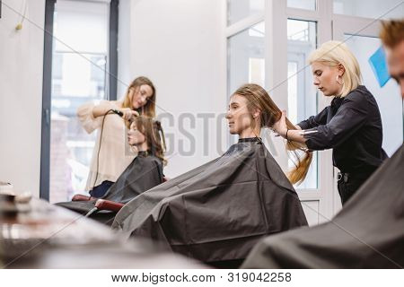 Beautiful Woman Combing Wet Hair. Stylist Brushing Woman Hair In Salon. Hairdresser Serving Customer