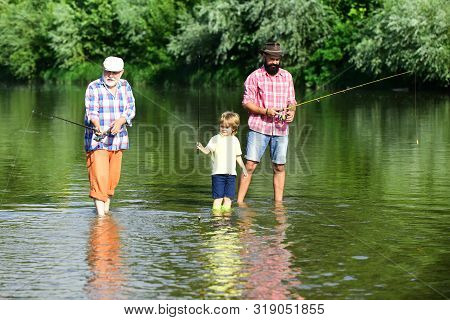 Great-grandfather And Great-grandson. Grandson With Father And Grandfather Fishing By Lake. Happy Gr